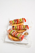 Marinated sausage skewers with vegetables on toast