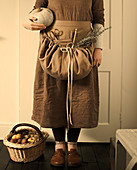 Woman wearing brown clothing holding pumpkin and with basket of freshly picked apples