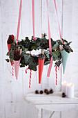 Hängender Efeu-Kranz weihnachtlich dekoriert mit Spitztüten und Zuckerstangen