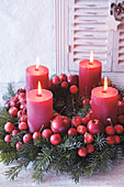 Adventskranz mit roten Zieräpfeln und roten Stumpenkerzen