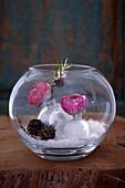 Selbstgemachte Schneekugel dekoriert mit Ranunkelblüten und Lärchenzweigen