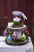 Weihnachtliche Etagere aus Baumscheiben dekoriert mit Windlicht und Baumschmuck