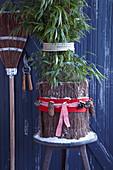 Zusammengebundene Bambuspflanze mit weihnachtlich dekoriertem Winterschutz