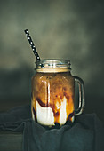 Iced caramel macciato coffee with milk in glass jar with straw on dark rustic wooden table