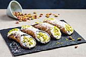 Italian sicilian cannoli with sweet ricotta cheese, chocolate chips and garnished with chopped pistachios and icing sugar