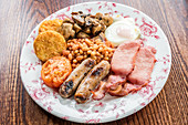 Traditional english breakfast with bacon, sausages, grilled tomato and mushrooms, baked beans, potato hash browns cakes and egg on a wooden table