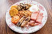 Traditionelles englisches Frühstück mit Speck, Würstchen, Tomaten, Pilzen, Baked Beans, Rösti und Ei