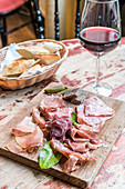 Board with cold meats and charcuteries, salami, prosciutto with bread in the background