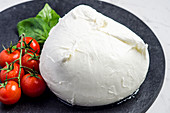 Fresh mozzarella garnished with cherry tomatoes and basil leaves on a dark stone plate
