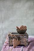Dekoherzen mit Waffelmuster in einer Schale auf einer alten Kiste