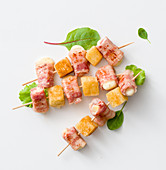 Mozzarella and bacon rolls with bread on skewers