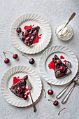 Chocolate, amaretto and cherry brownie with cream and fresh cherries, sliced