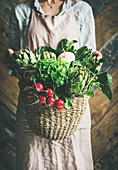 Female farmer in linen apron holding basket of fresh garden vegetables and greens in her hands