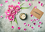 Tasse Kaffee, umgeben mit rosa Tulpen und Smiley auf Papier
