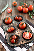 Tomatoes in a metal tray on a wooden background