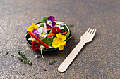 Rocket and cucumber salad with peppers, pine nuts and edible flowers