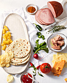 Ingredients for lunch (tortilla, ham, tuna, cheese, vegetables)