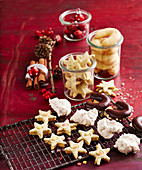 Various Christmas biscuits on a wire rack and in jars