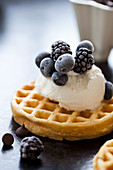A waffle topped with ice cream and frozen blackberries