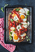Pizza with egg, bacon, cherry tomatoes and mozzarella