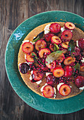 Polenta cake with fresh plums and pomegranate seeds
