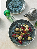 Arabian wild rice salad with dried sour cherries, sesame seeds, goat's cheese balls, spring onions and mint