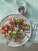 Napkin dumplings with water cress, onions, radishes and beef stripes