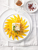 Grilled mango carpaccio with pink pepper and goat's cheese