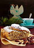 A mini cranberry and pecan nut stollen for Christmas on baking paper in front of a cup of coffee