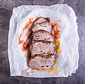 Slices of baked roasted pork meat on parchment with mustard and ketchup