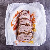 Kalte Schweinebratenscheiben auf Pergamentpapier mit Senf und Ketchup
