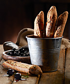 Olive baguettes in a metal bucket with black olives