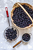 Blackberry in a basket and a sieve on a concrete background
