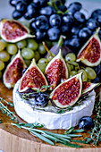 Cheese Camembert with figs, honey, grapes and fragrant herbs
