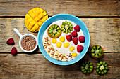 Frühstücks-Porridge mit Kiwi, Mango, Himbeere, Banane und Leinsamen