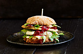 A chicken burger with camembert and cranberry sauce