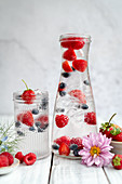 Water with fresh berries and ice cubes