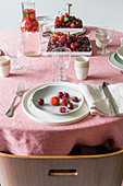 Table set with berries and pink tablecloth