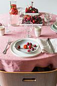 Gedeckter Tisch mit Beeren und Tischdecke in Rosa