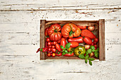 Various types of tomatoes in a crate on a light wooden background