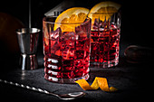 Classic Italian cocktail: Negroni on ice with oranges in glasses