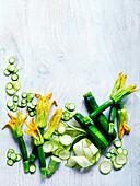 Zucchini-Stillleben mit Zucchiniblüten und Zucchinischeiben
