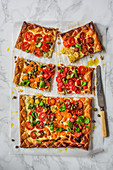 Puff pastry tomato tart with creme cheese, olives, capers and basil