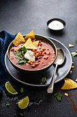 Spicy mexican bean soup with corander, tortillas and sour cream