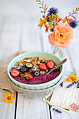 A smoothie bowl with cereal and berries