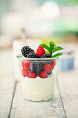 Cottage cheese with fresh berries and mint in a glass (low carb)