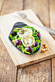 Raclette with savoy cabbage, goat's cheese, walnuts and grapes