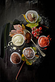 Ice cream desserts and vanilla sauce in paper cases, grapes and autumnal leaves on a black surface