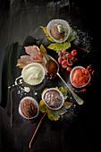 Eisdessert und Vanillesauce in Papiermanschetten, Weintrauben und Herbstlaub auf schwarzem Untergrund
