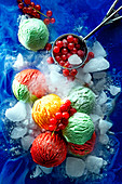 Colourful scoops of ice cream with ice cubes and redcurrants on a blue surface